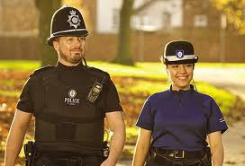 Police man and woman smiling in sun light